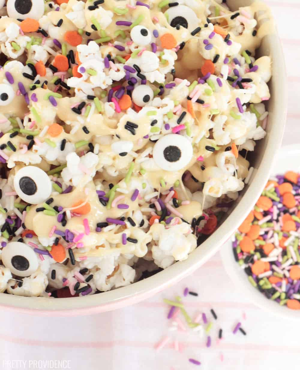 Spooky Halloween Popcorn with melted marshmallow, Halloween sprinkles and candy eyeballs on it.