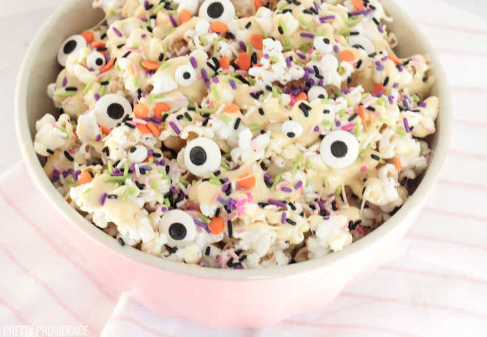 Monster Marshmallow Popcorn with Halloween sprinkles in a pink mixing bowl.