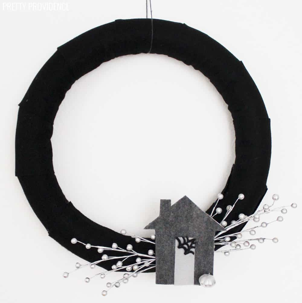 Black Halloween Wreath with a grey felt Haunted House and silver berries hanging on a white wall.