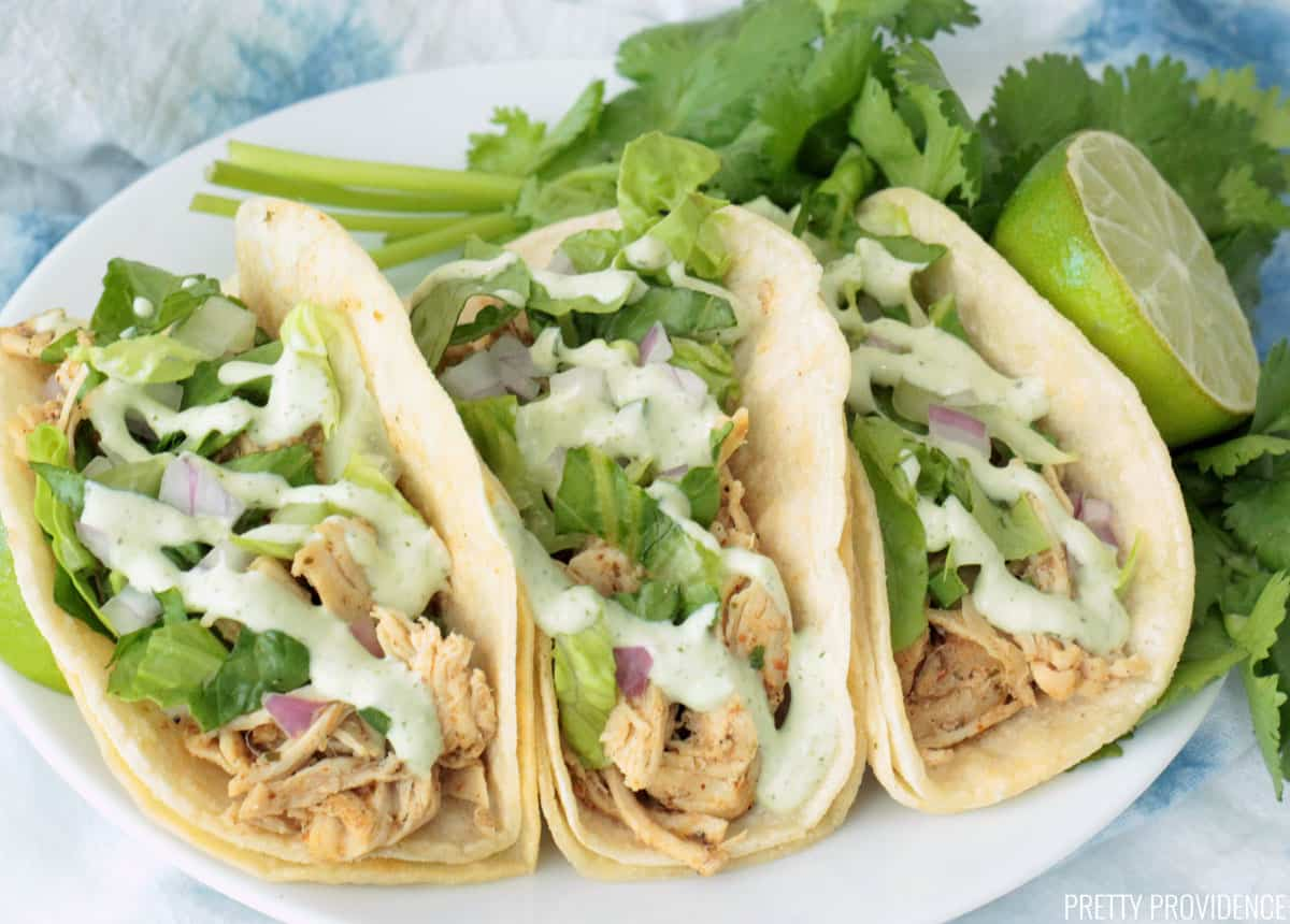 Three shredded chicken tacos topped with lettuce, onion, and jalapeño ranch taco sauce