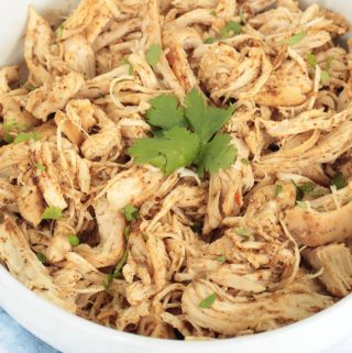 Crockpot shredded chicken for tacos in a white bowl with cilantro on top