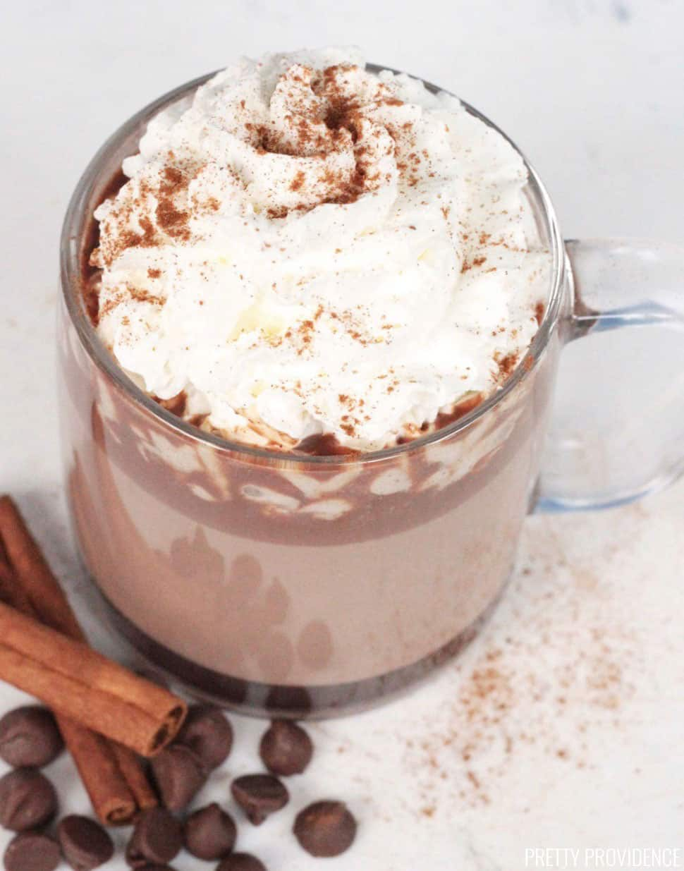 Pumpkin Spice Hot Chocolate with cinnamon sticks and chocolate chips and whipped cream on top with pumpkin pie spice dusted on top.