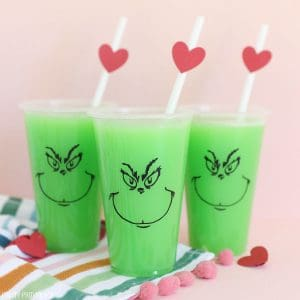 Bright green punch in clear party cups with The Grinch face on them and red hearts on the straws