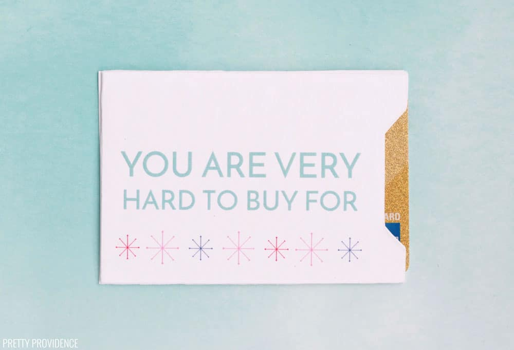 "White gift card envelope with 'You Are Very Hard to Buy For"" in blue text with snowflakes on a blue background."