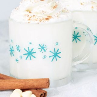 White Hot Chocolate in mugs with whipped cream and cinnamon. White chocolate chips on the side of the mugs.