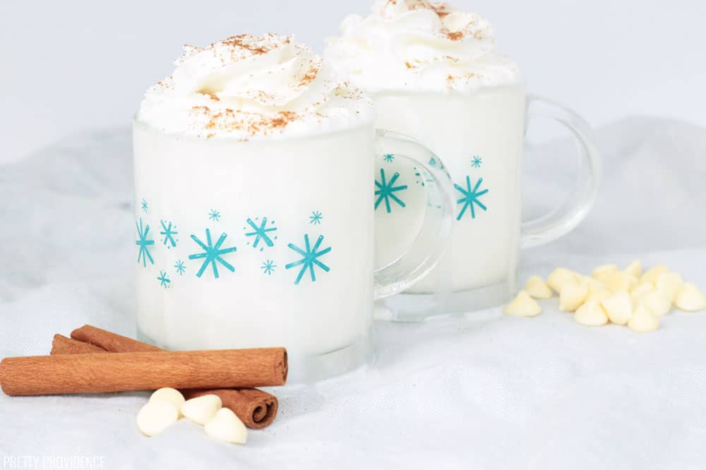 Two mugs of White Hot Chocolate with whipped cream on top, dusted with cinnamon and two cinnamon sticks and white chocolate chips on the side.