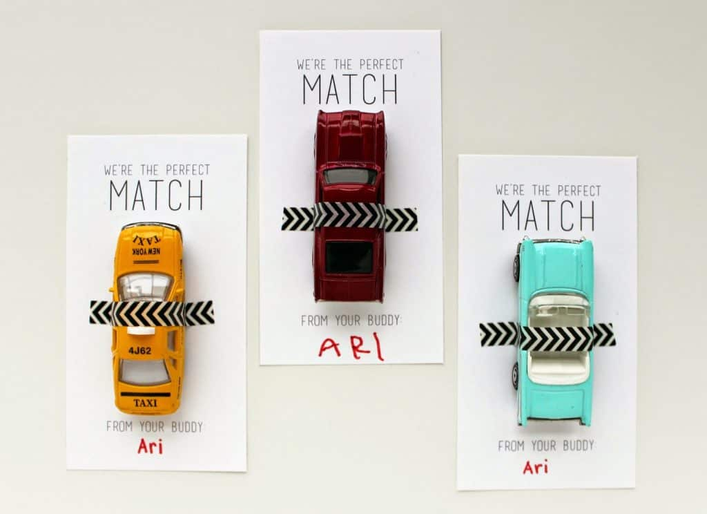 three matchbox car valentines for kids, one yellow car, red car and teal car with washi tape to hold them onto the cards.