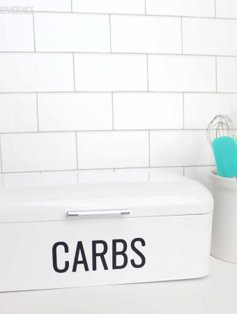 retro bread box with 'carbs' vinyl label on it on a white countertop