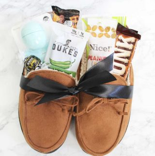 Men's moccasin slippers filled with treats and small gifts tied with a black ribbon