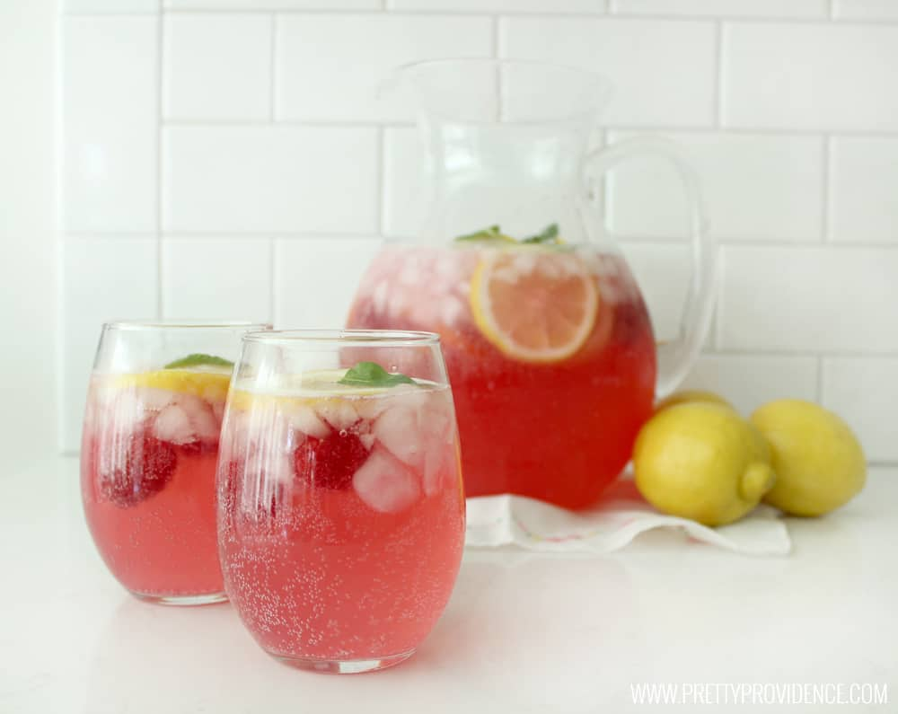 a pitcher of raspberry lemonade next to some lemons with two filled glasses of lemonade in the foreground.