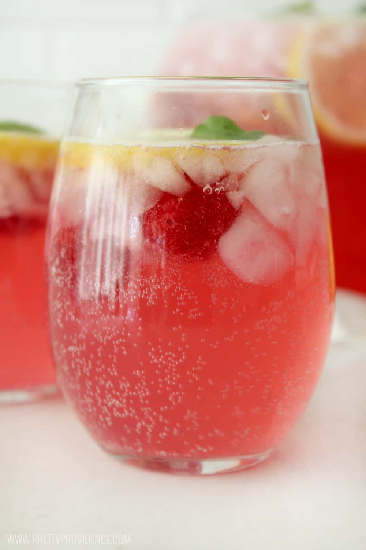 Raspberry, ice and lemon floating in a glass of homemade raspberry lemonade
