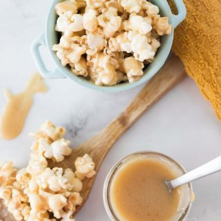 homemade caramel next to a bowl and a spoon filled with caramel popcorn