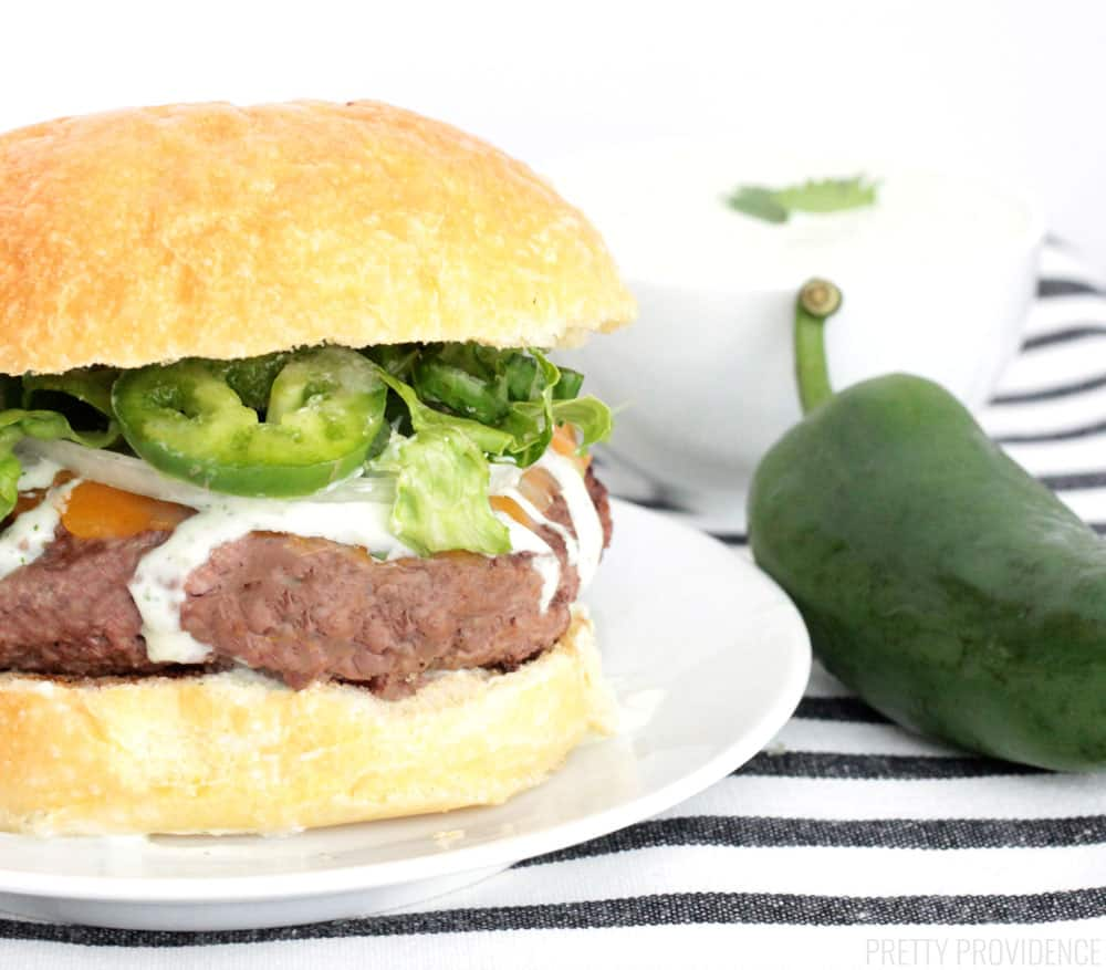 Cheeseburger with a white plate topped with jalapeño ranch, jalapeño peppers, and lettuce on a brioche bun.