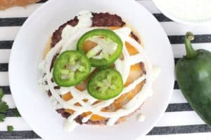 Angus beef patty on a white plate, topped with melted cheese, jalapeño ranch, onions and jalapeño peppers.