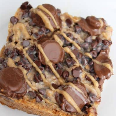 These peanut butter magic bars are to die for! Like magic cookie bars but with Reeses minis + melted peanut butter!