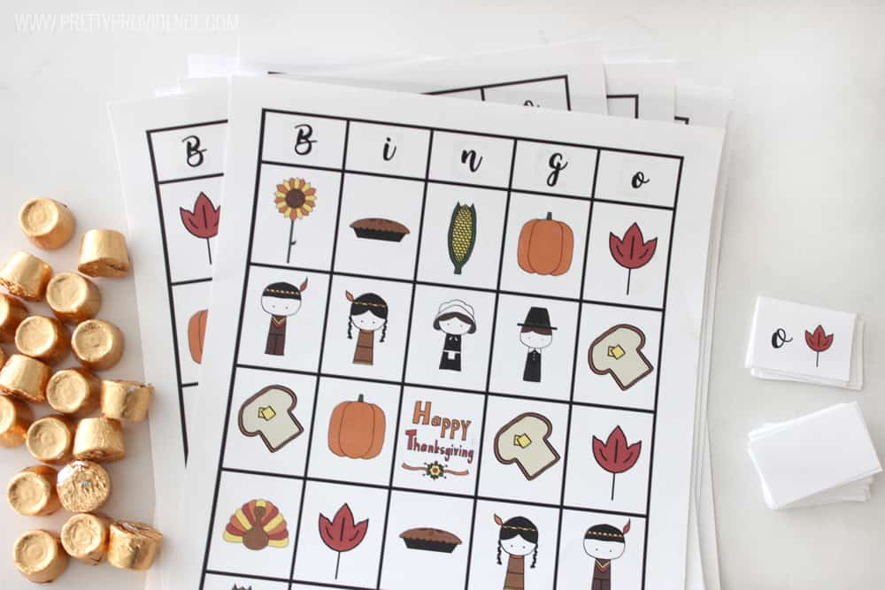 Thanksgiving Bingo free to print sheets stacked with gold-wrapped Rolo candy on the side.