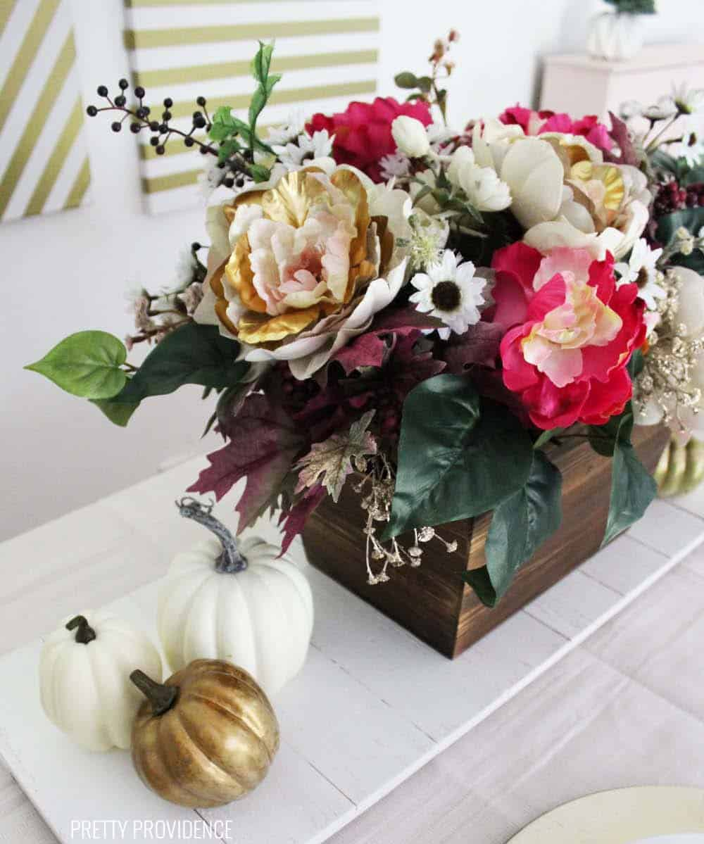Fall floral arrangement centerpiece, with gold and cream peonies, pink, white flowers and gold berries.