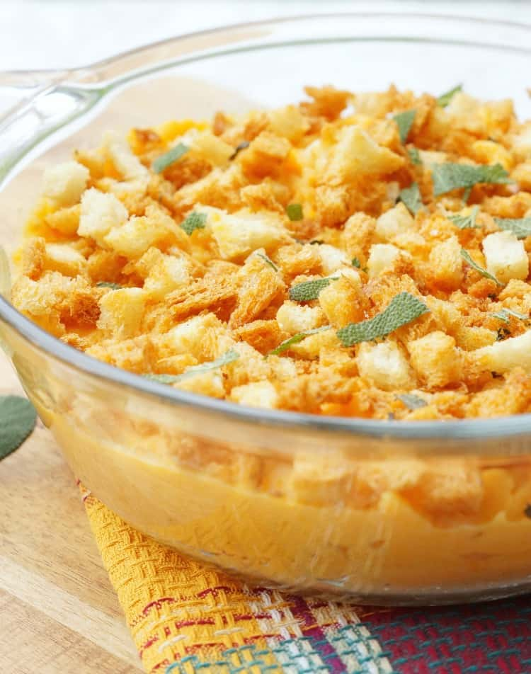 Close up of savory sweet potato casserole in a glass dish with breadcrumbs and sage on top.