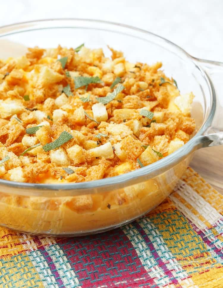 Savory Sweet Potato Casserole in a glass dish with sage breadcrumbs and fresh sage leaves on top.