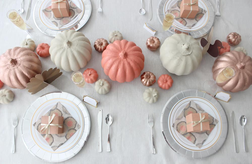 Thanksgiving table overhead view. White plates, silver chargers, orange, cream and copper pumpkins and Thanksgiving favor boxes on each plate.