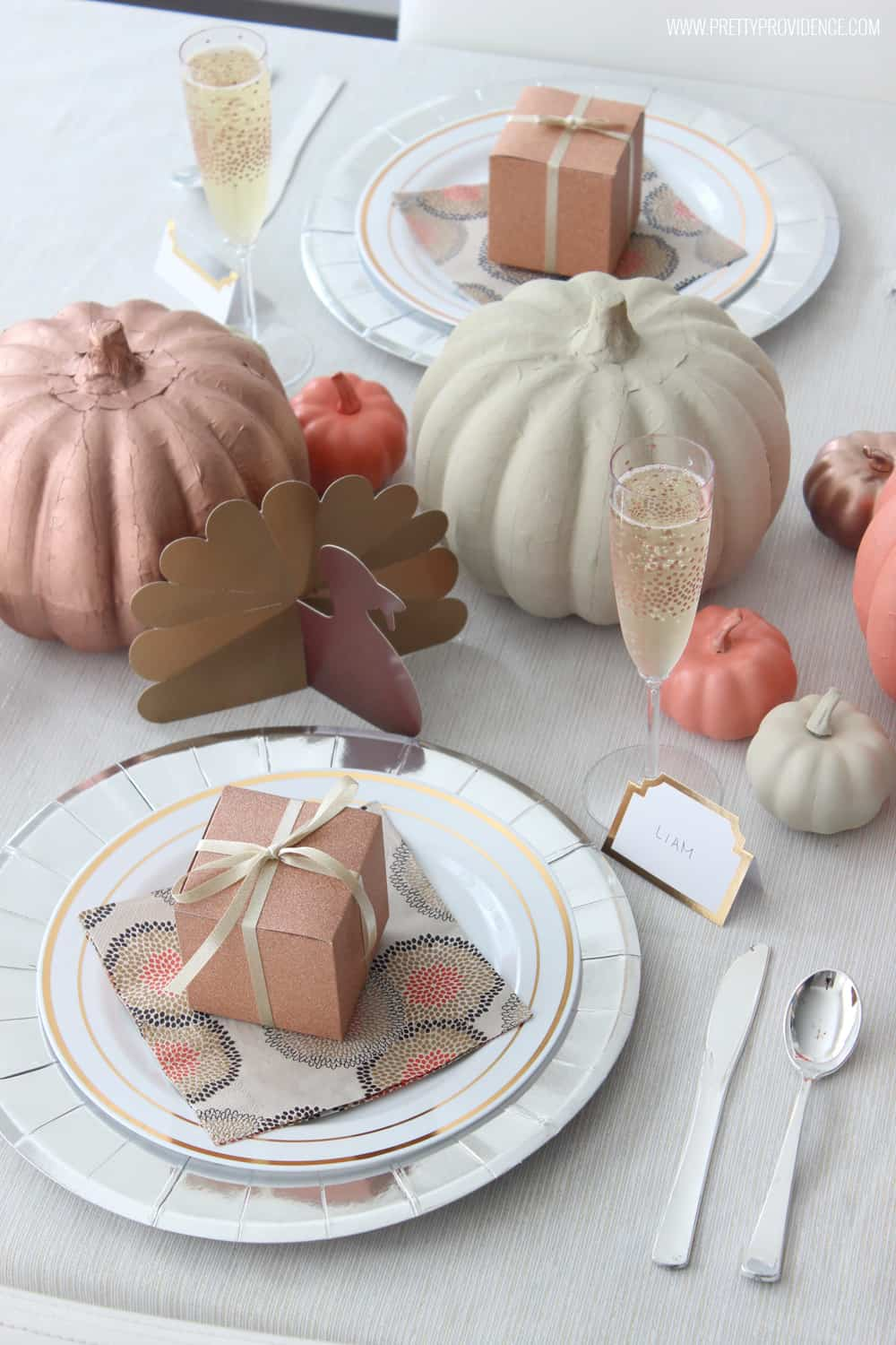 Thanksgiving table set with paper products - silver, white and copper craft pumpkins and paper turkeys.