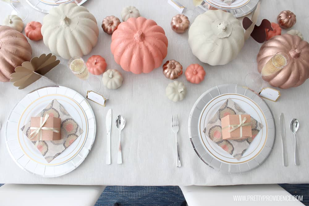 Thanksgiving Table set with paper products, overhead view. Orange, gold and cream pumpkins, silver chargers, and more.