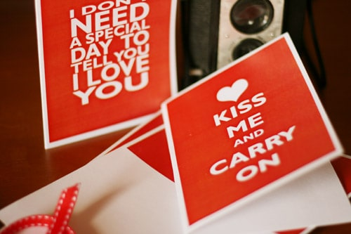 Valentine Card red with white letters that reads Kiss Me & Carry On inspired by the Keep Calm & Carry On posters well-known in pop culture.