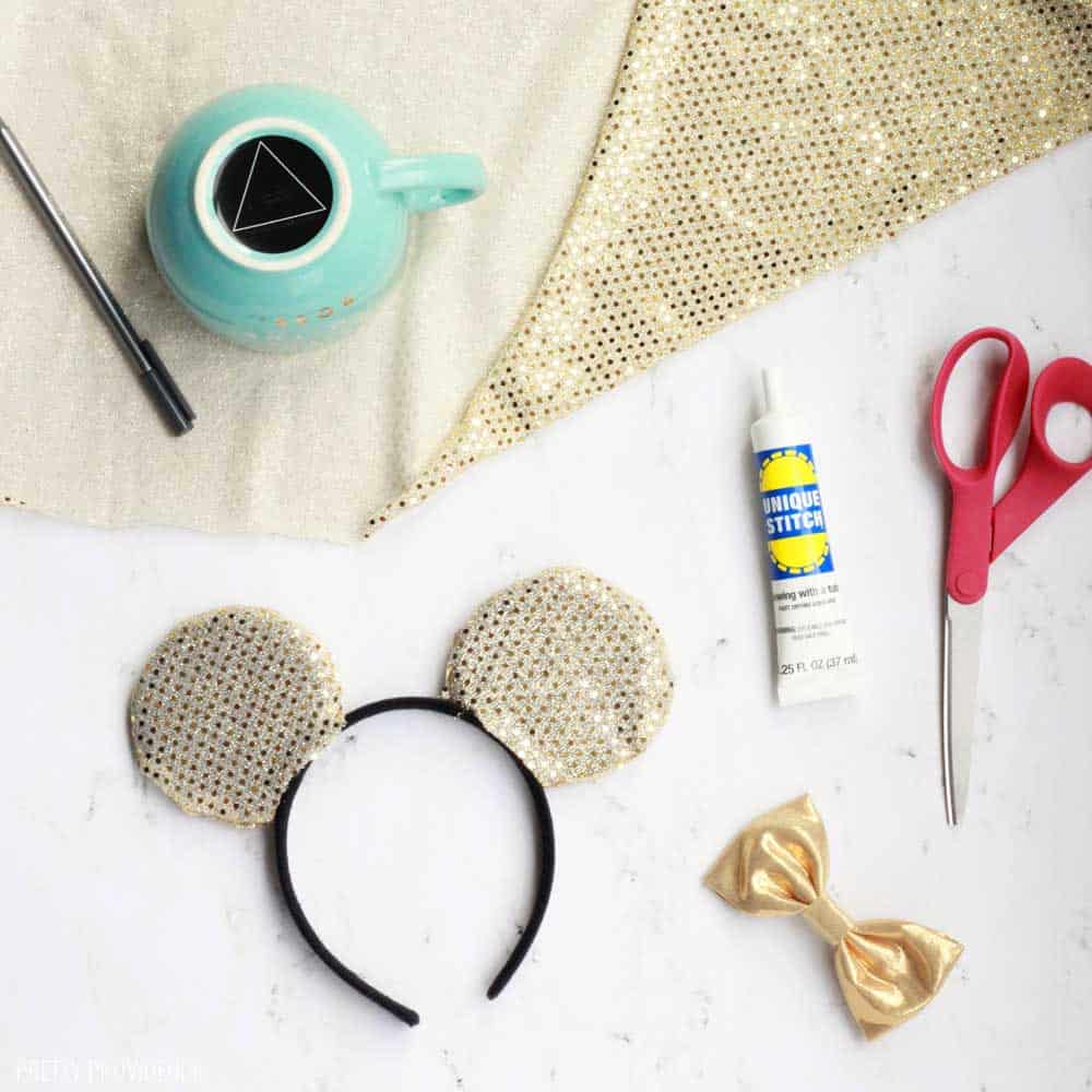 gold fabric, scissors, blue, a gold bow and some minnie mouse ears on a white counter