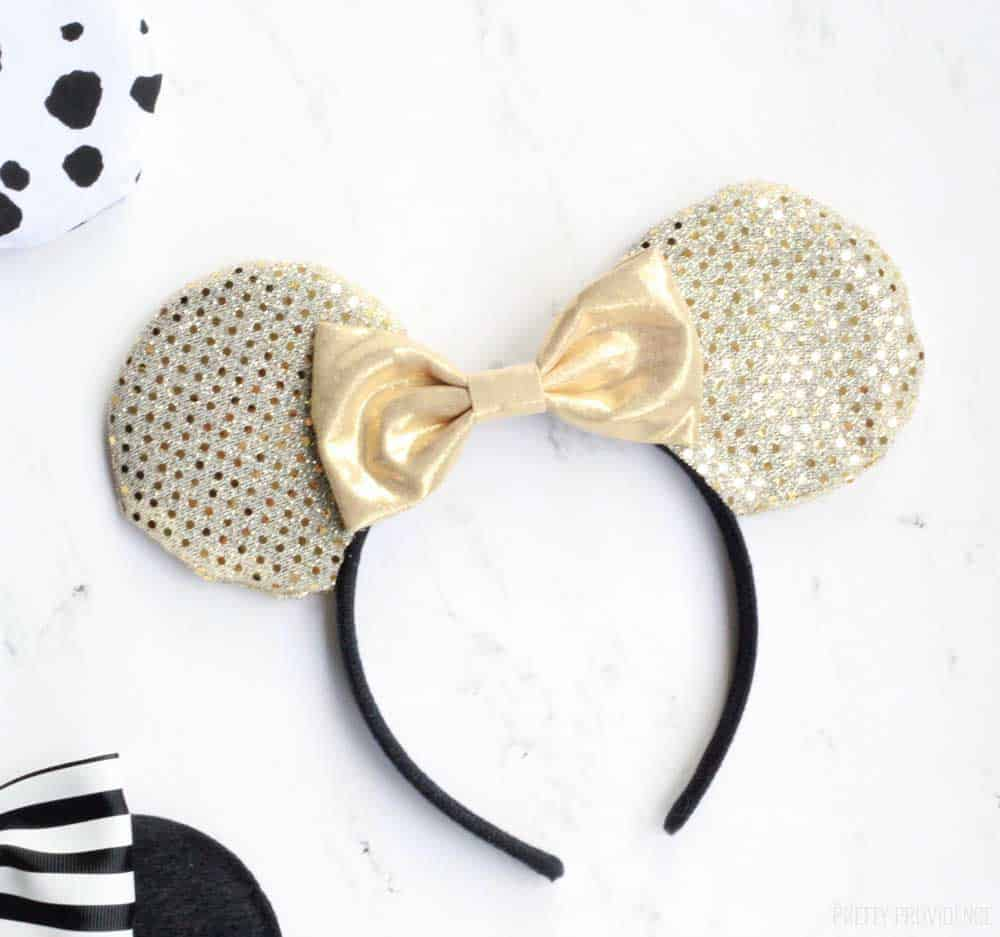gold minnie mouse ears with a gold bow on a white countertop