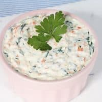Healthy veggie dip made with yogurt, sautéed vegetables, in a pink bowl and parsley as a garnish.