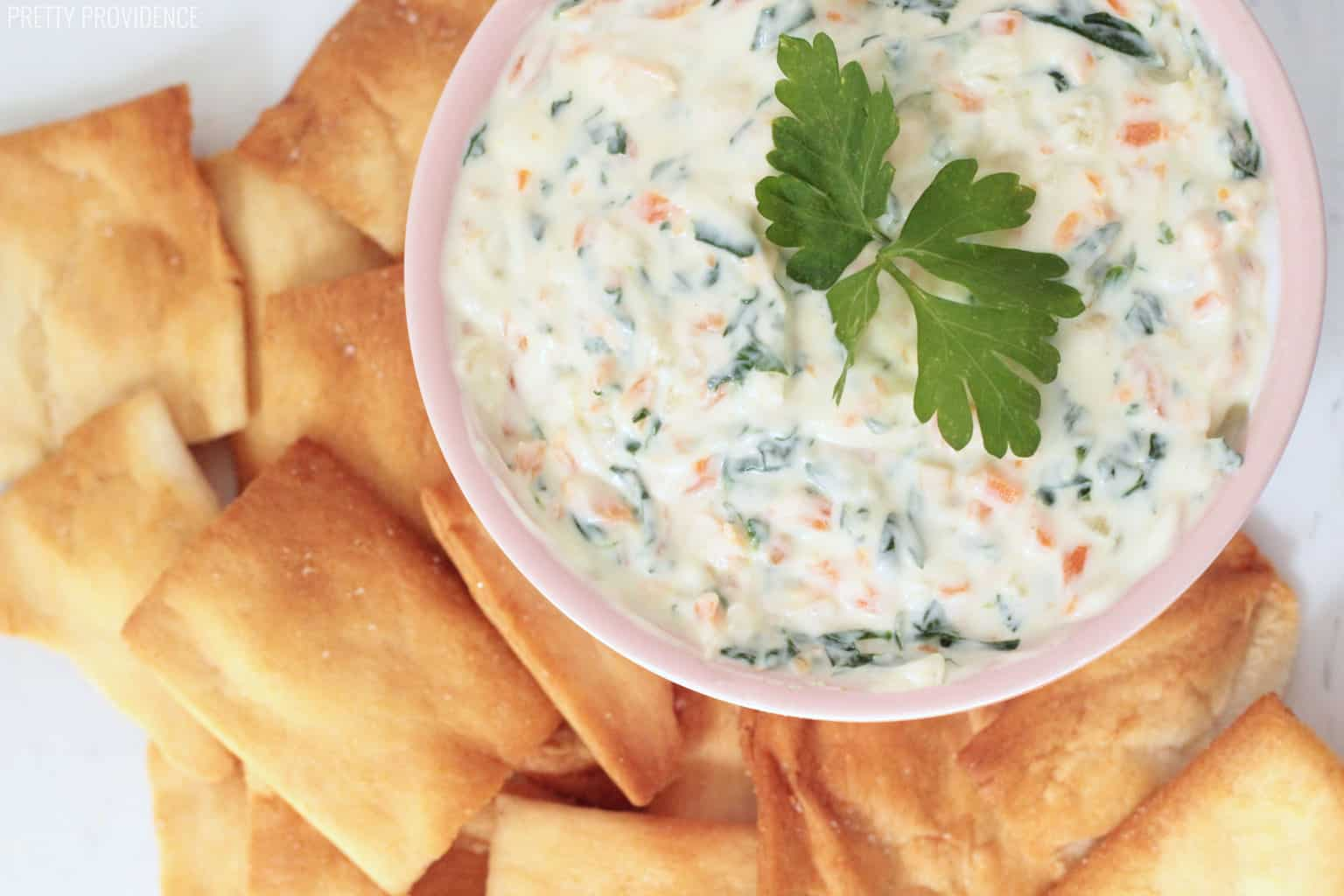 Healthy Veggie Dip in a pink bowl, parsley garnish on top and pita chips around the bowl.