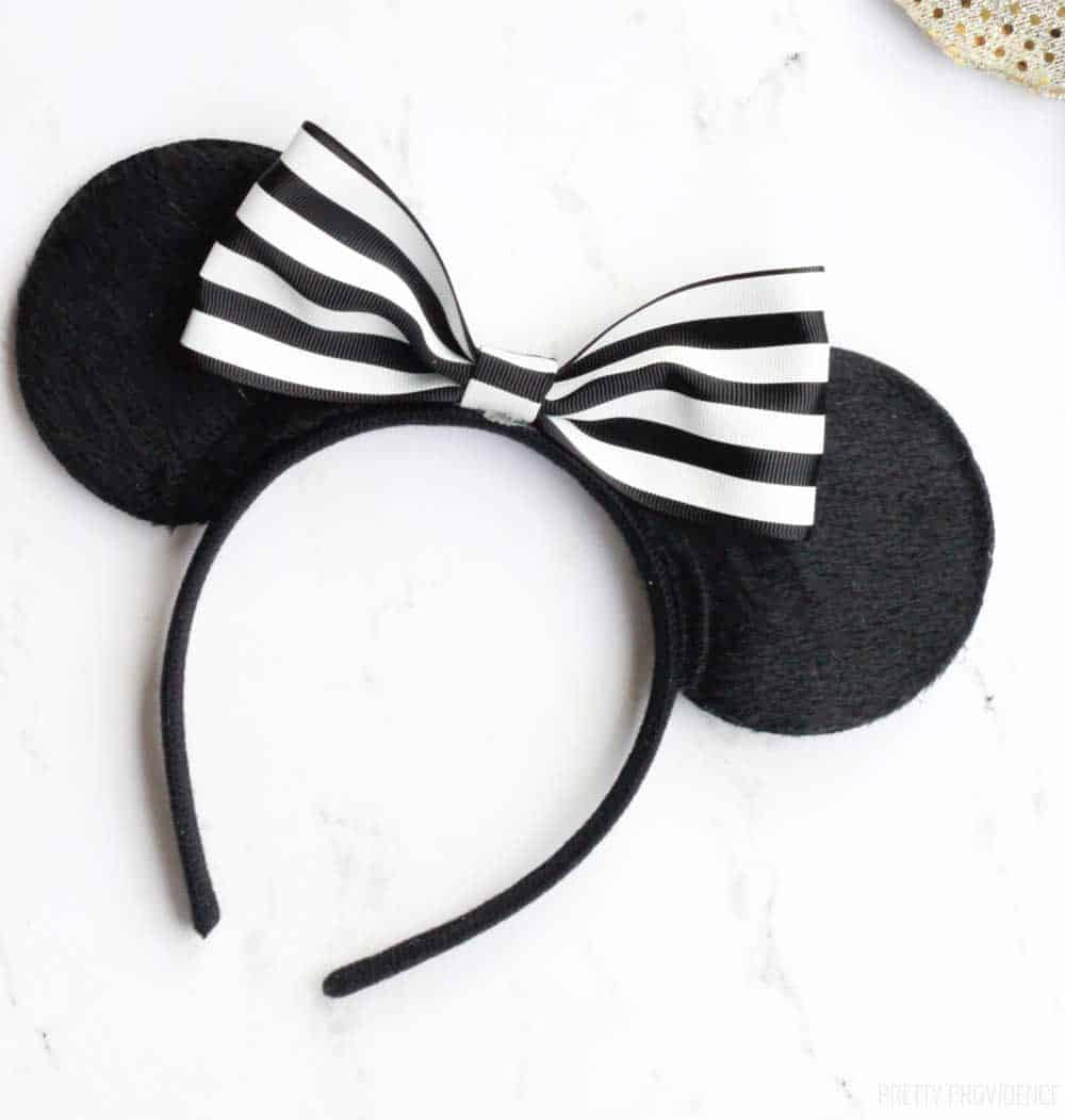 black minnie mouse ears with a diy black and white striped bow on a white counter