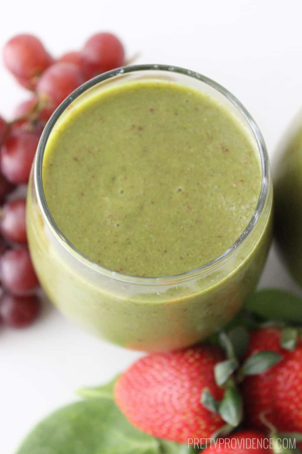 Green smoothie in a clear glass, with red grapes and strawberries on the side.