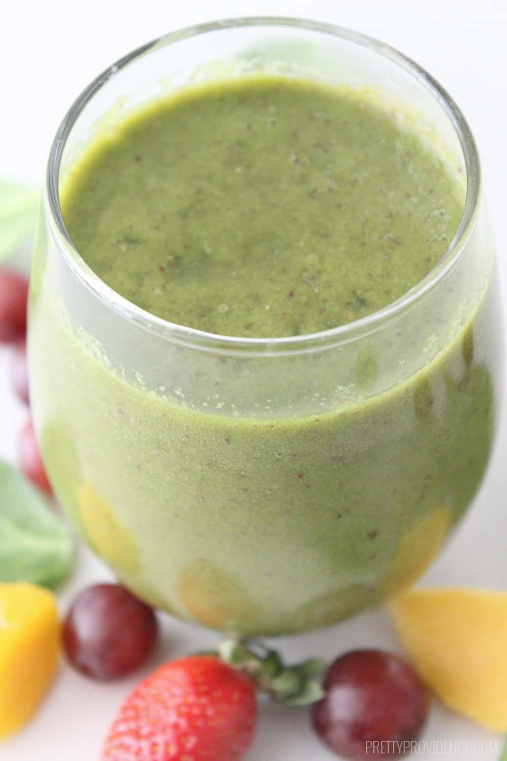 Green Smoothie in a clear glass surrounded by fresh fruit and spinach.