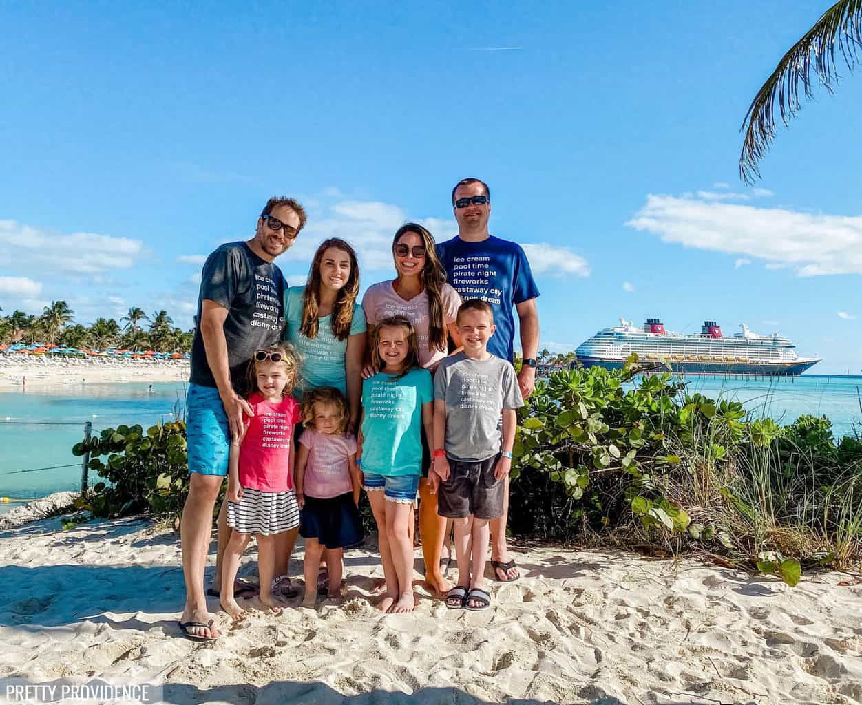 Family wearing matching disney cruise family shirts on Castaway Cay with Disney cruise ship in the background.