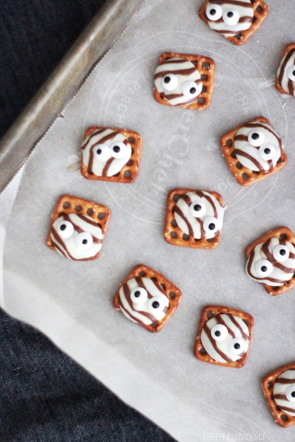 monster pretzel hugs lined up on a parchment covered cookie sheet