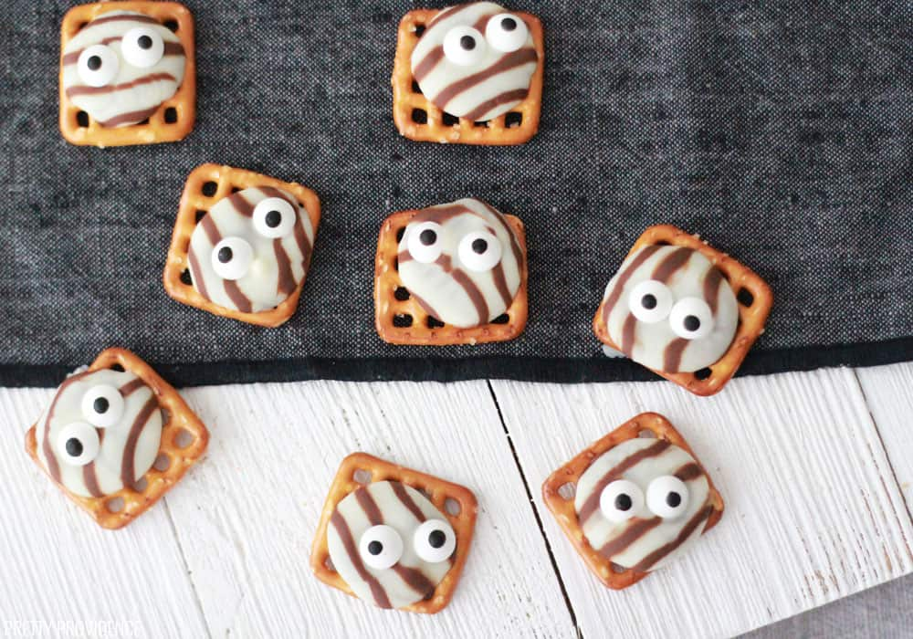 pretzel hugs with eyes for halloween on a white table with a black runner