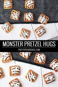 pretzel hugs with candy eyeballs on a white wood table by a black runner