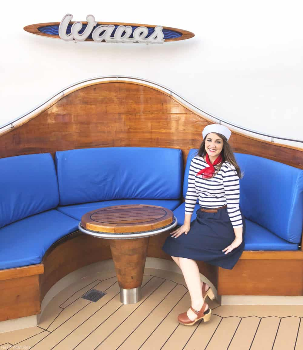 a girl in a sailor costume sitting on a restaurant booth with blue cushions