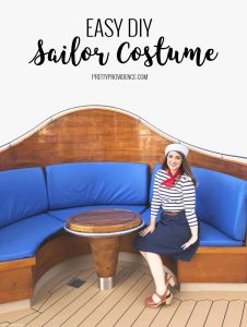 a girl in a sailor costume sitting on a blue cushioned restaurant booth