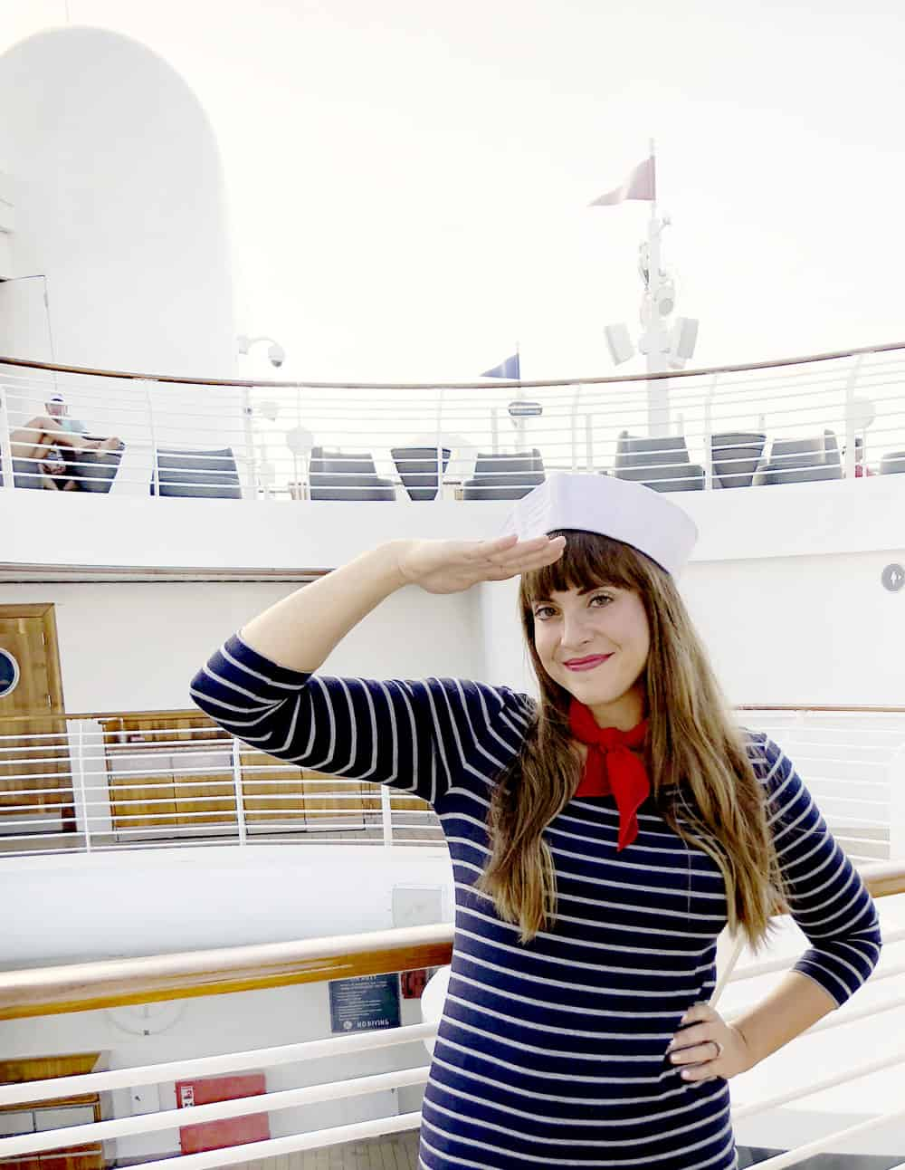 a brown haired girl in a sailor costume saluting on the deck of a ship