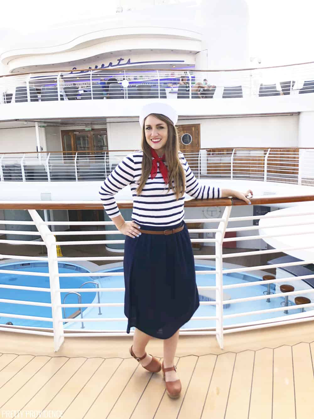 a girl on the deck of a ship posing in a sailor costume
