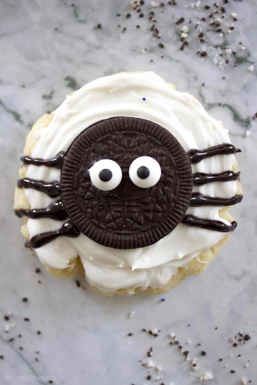sugar cookie with an oreo spider on top sitting on a granite counter