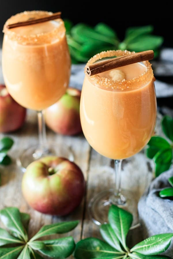 Caramel Apple Mocktails in wine glasses, with sugar on the rim and cinnamon sticks as garnish, and apples on the table.