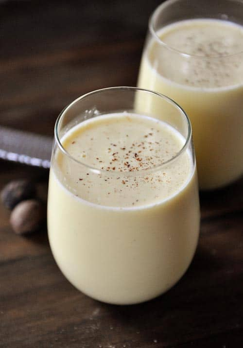 Homemade Eggnog in clear wine glasses dusted with nutmeg.