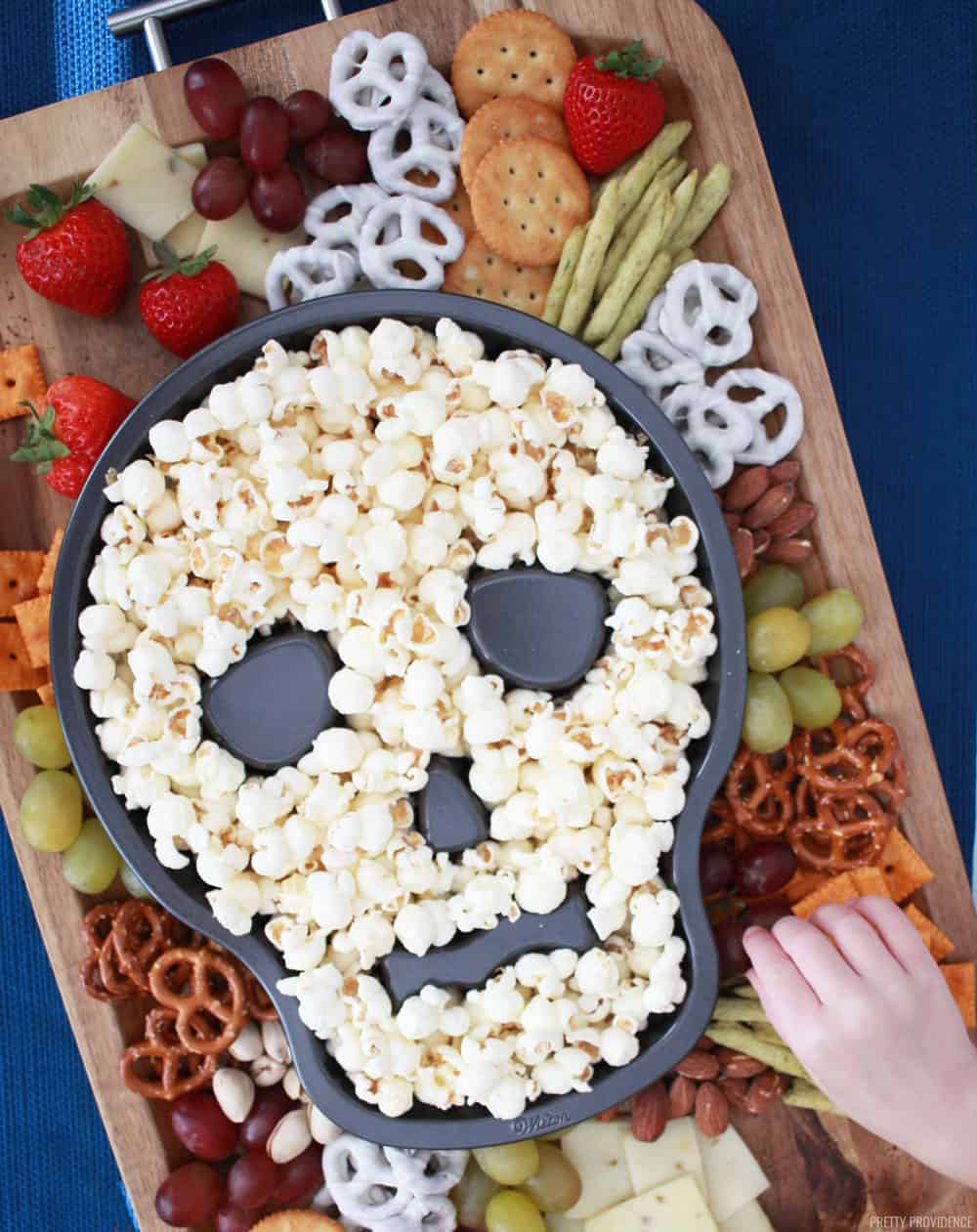 Halloween Snacks like pretzels, fruit, crackers and cheese on a serving board and popcorn in a skull shaped cake pan in the middle.