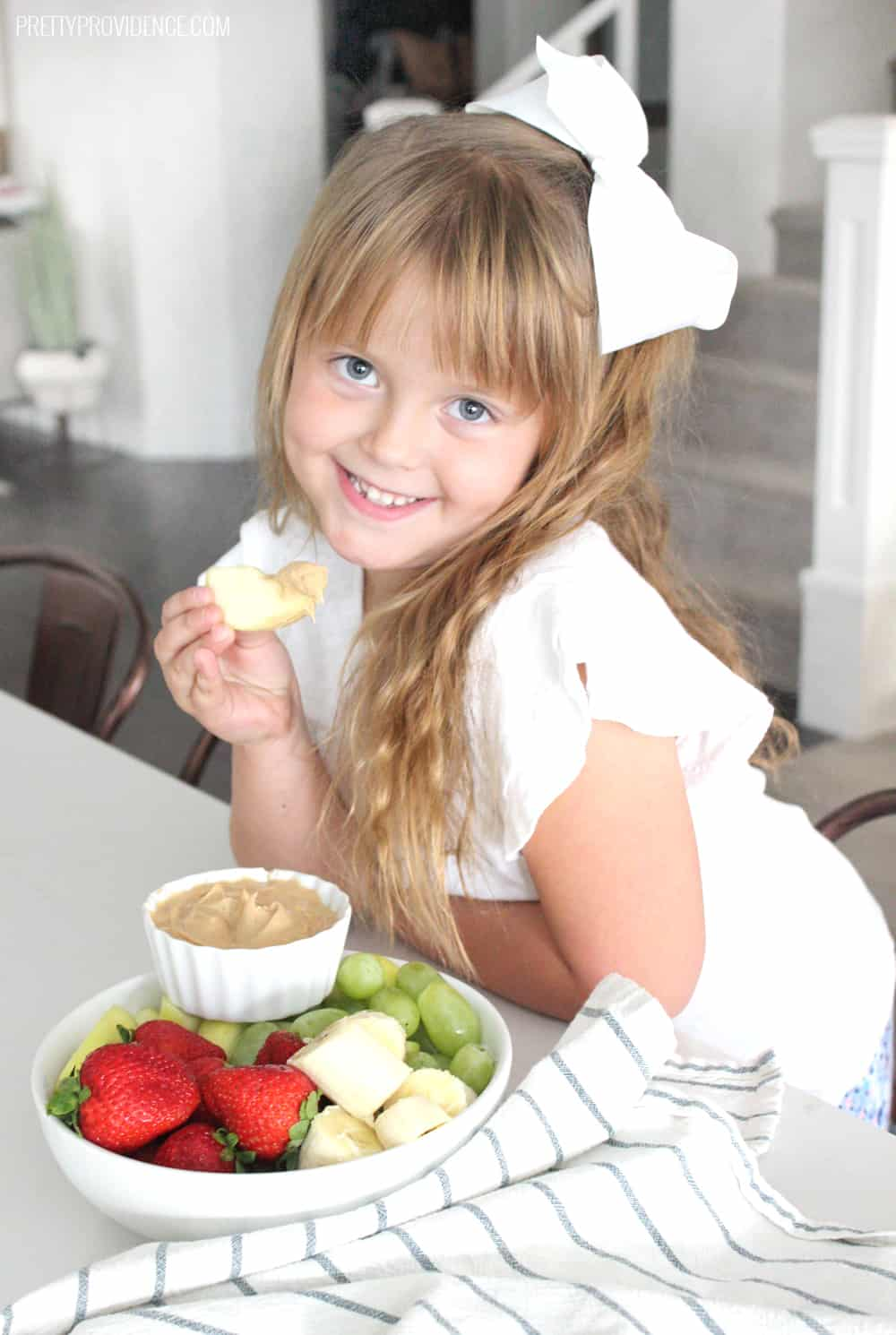 Little girl in white shirt eating strawberries, bananas, grapes and peanut butter dip.