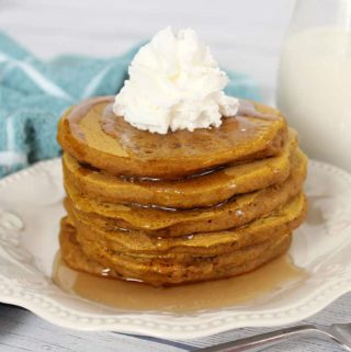Pumpkin Pancakes stacked high on a white plate with syrup and whipped cream on top.