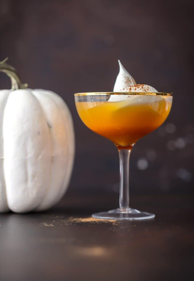 Pumpkin mocktail in a clear cocktail glass, topped with whipped cream and dusted with nutmeg.