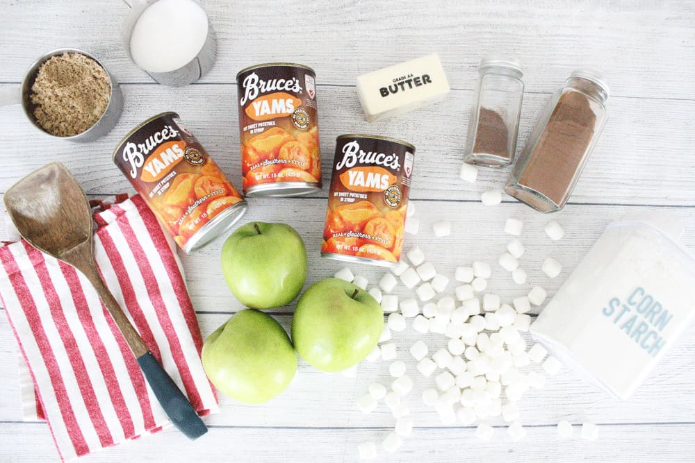 apples, sweet potatoes, marshmallows, cinnamon, butter, sugar and a red and white striped tea towel on a wooden counter